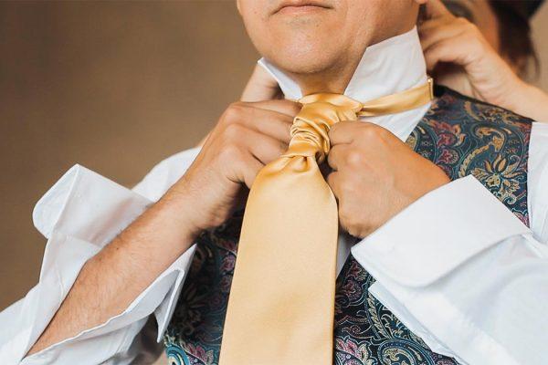 Preparación del novio atando la corbata
